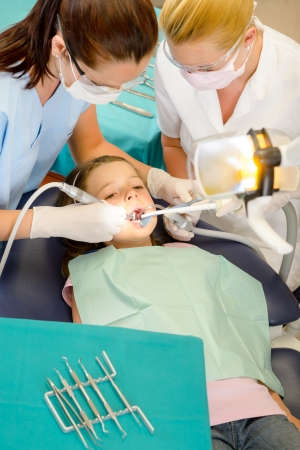 Dentist and assistant with little girl patient  at stomatology clinic Stock Photo - 13769805