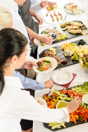 party food: Business people around buffet table catering food at company event