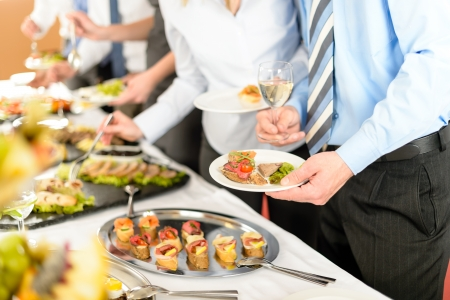 lunch meeting: Catering at business company event people choosing buffet food appetizers Stock Photo