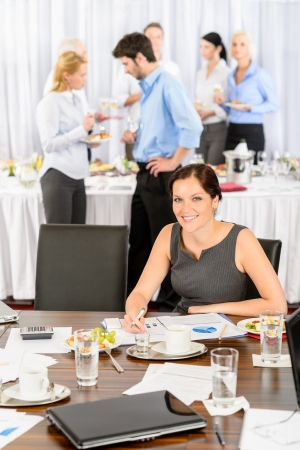 Business woman at company event work during buffet lunch photo