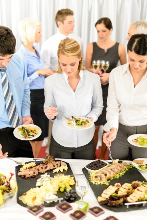 Company meeting catering smiling business people eat buffet appetizers photo
