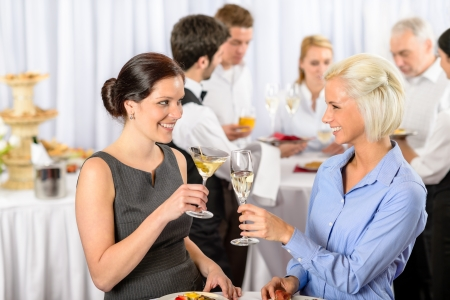 Business event two female colleagues celebrate enjoy catering buffet