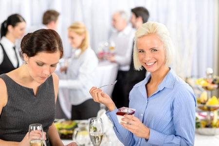 Business meeting buffet smiling woman eat dessert formal company event photo
