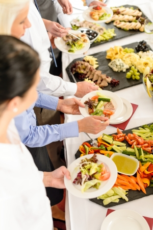 serving tray: Business people around buffet table catering food at company event