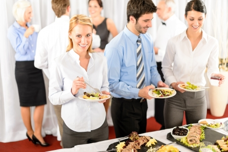 business event: Business colleagues serve themselves at buffet catering service company event Stock Photo
