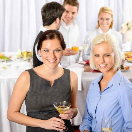 company party: Two business woman smiling at catering buffet company meeting