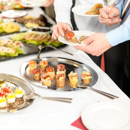 buffet food: Catering at business company event people choosing buffet food appetizers Stock Photo