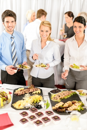 lunch tray: Company meeting catering smiling business people eat buffet appetizers
