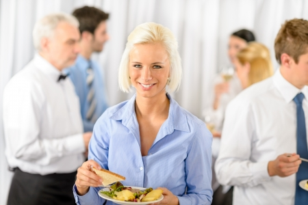 Smiling business woman during company lunch buffet hold salad plate photo
