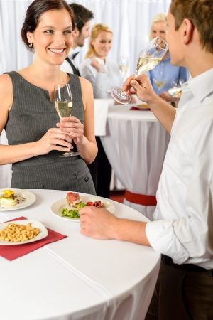 company party: Business event two colleagues celebrate drink champagne enjoy catering buffet Stock Photo