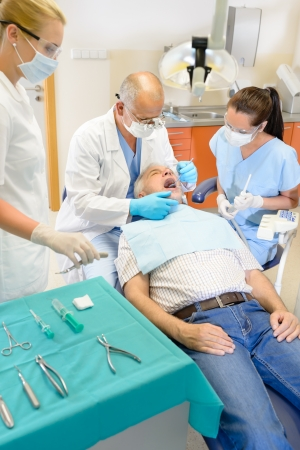 practitioner: Senior man at dentist surgery having tooth operation stomatology clinic