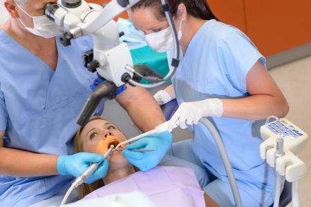 laboratorio dental: Dentista del paciente femenina de funcionamiento a trav�s del microscopio en el consultorio de cirug�a Foto de archivo