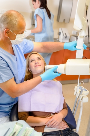 dental nurse: Dentist taking x-ray of female patient with nurse assistance