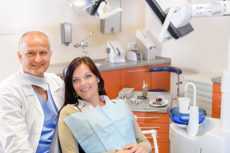 Woman at dental clinic surgery with male stomatology hygienist photo