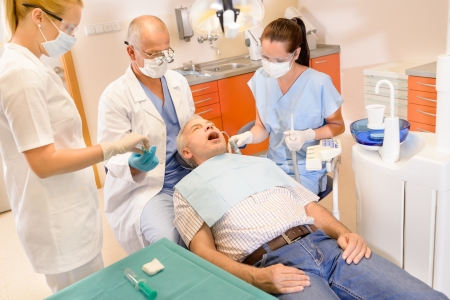 Senior man at dentist surgery having teeth checkup dental assistant photo