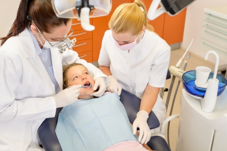 Dental assistant with dentist female and little child at stomatology surgery photo