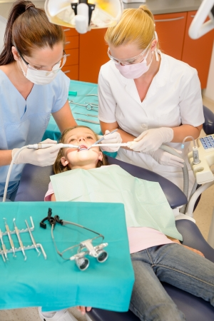 dentist drill: Dentist and nurse doing operation on child patient