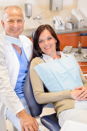 checkup: Woman at dental clinic surgery with male stomatology hygienist