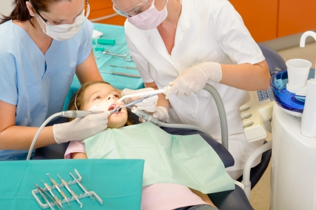 Dentist and assistant with little girl patient  at stomatology clinic photo