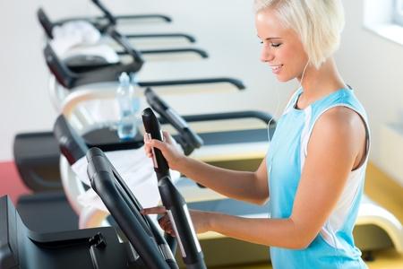 eliptica: Gimnasio joven mujer en la cruz entrenador elíptica en el gimnasio de la salud Foto de archivo