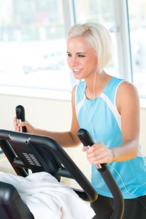 eliptica: Mujer joven en la máquina de ejercicios de fitness cardio en club deportivo