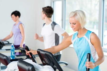 Walking on treadmill young people running exercise at fitness center photo