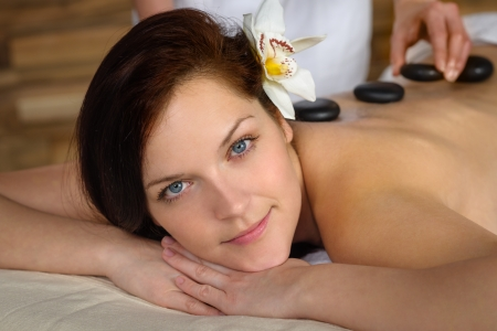 Woman with flower at spa having hot stone back treatment Stock Photo - 30203778