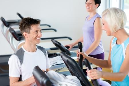 aide � la personne: Marcher sur le tapis roulant d'entra�nement jeune gens � un centre de fitness cardio Banque d'images