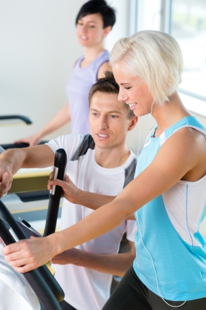 Walking on treadmill young people cardio workout at fitness center photo