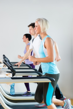 Running on treadmill young people exercise at fitness center Stock Photo - 13969400