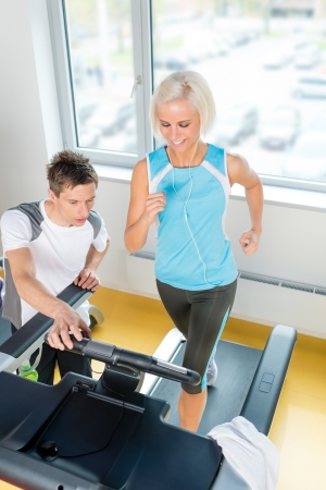 Young personal trainer instruct woman running at fitness center