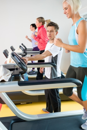 instruct: Young personal trainer instruct woman running at fitness center