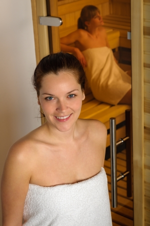 wrapped in a towel: Young woman wrapped in towel posing in front of the sauna room Stock Photo