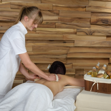 Beautiful brunette having wooden brush massage at luxury spa photo