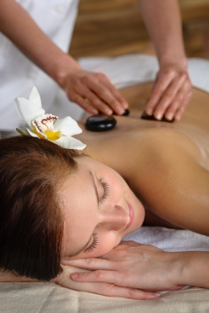 Woman with flower at spa having hot stone back treatment photo