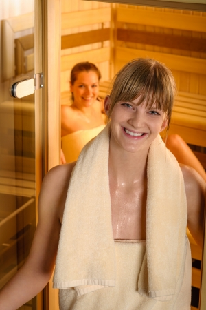 Smiling woman wrapped in towels at sauna room photo