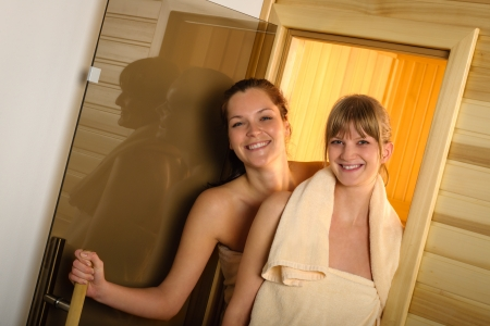 Happy women getting out of sauna at spa center photo