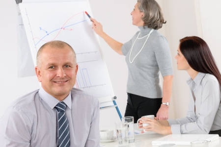 flip chart: Smiling businessman during team meeting with colleagues give presentation
