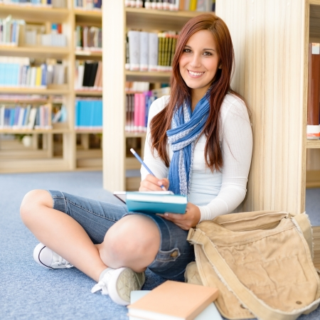 school room: Female high school student at library sitting on the floor