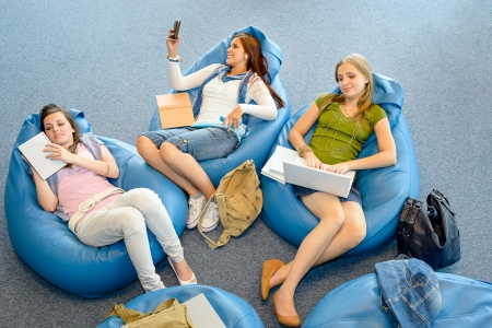 Young student girls resting on blue beanbags at library photo