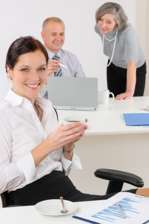 Professional businesswoman attractive drink coffee sitting by office desk photo