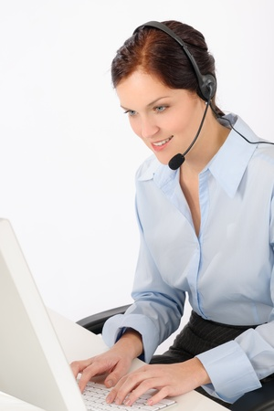 Friendly help desk woman at call center sitting behind computer photo