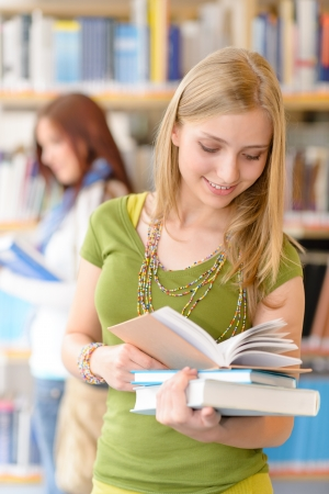 Happy female blonde student at library with books high school photo