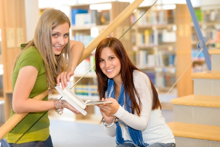 Two young student girls on high school library stairs photo