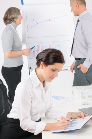 Giving presentation young executive during meeting woman review charts photo