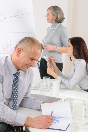 Mature businessman during team meeting with colleagues give presentation photo