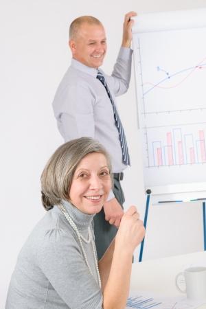 Giving presentation executive businessman during meeting write flipchart photo