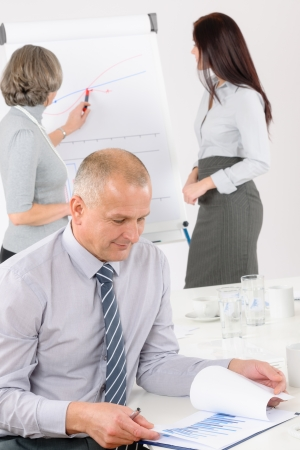 Giving presentation mature executive during meeting woman pointing flip chart Stock Photo - 14077425