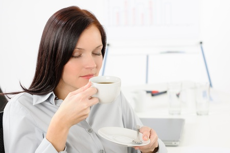 Attractive businesswoman drink coffee at modern office enjoy break photo