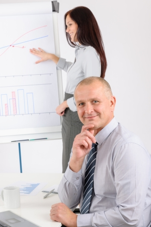 Giving presentation mature executive during meeting woman pointing flip chart Stock Photo - 14091359